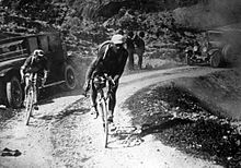 Black and white image of cyclists on a sandy road.