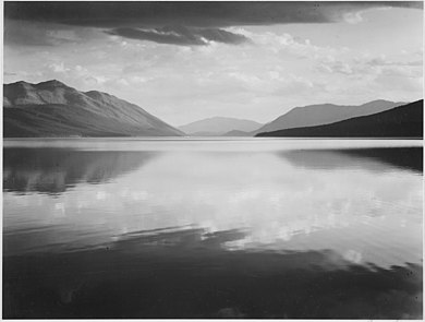 A black-and-white photograph shows a large, still lake extending horizontally off the frame and halfway up vertically, reflecting the rest of the scene. In the distance, a mountain range can be seen, with a gap in the center and one faint smaller mountain in between. The sky is cloudy and large dark clouds rest at the very top of the frame.
