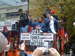 """Group of men on a raised platform. One holds a sign that reads """"JETER is playing GOLF today"""" and """"THIS IS BETTER!"""""""