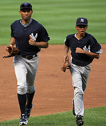 Mariano Rivera and his son wearing navy blue hats and baseball jerseys as they jog on a baseball field.