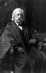 A man in his mid-fifties with bushy white hair, sideburns, and a mustache. He is sitting in a chair wearing a black judicial robe over a black suit and tie and white shirt.
