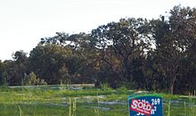 a grassed area in the foreground with a 'sold' real estate sign, against a background of banksia woodland
