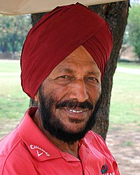 A Sikh man in his late 70s in a red turban and pink T-shirt with beards.