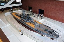 An overhead view of a very large warship model housed in a four-storey gallery. People are viewing the model and taking photographs.