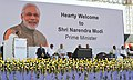 Narendra Modi addressing at the foundation stone laying ceremony for HAL Helicopter Factory, at Tumakuru, Karnataka. The Governor of Karnataka, Shri Vajubhai Rudabhai Vala, the Union Minister for Defence.jpg