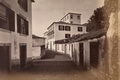 Narrow cobbled street flanked by white-washed buildings in Funchal (1880) - Reverend J N Dalton.png