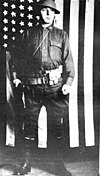 Oscar Pfaus in uniform, standing in front of a U.S. flag