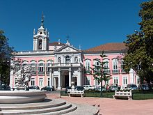 An ornate pink-and-white building in the baroque style is pictured from the front on a sunny day.