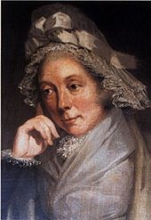 Quarter-length portrait, showing a woman in a brown and gray lace bonnet with a bow and leaning on her right hand.