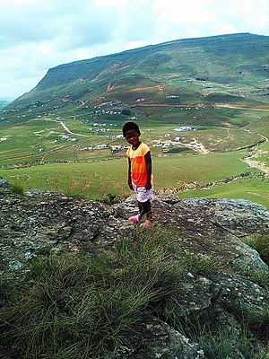 Qumbu - Photograph of the village of Qumbu in the background, with a local child in the foreground.
