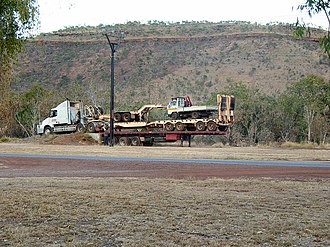 Road train - Double-stacked trailers (with a small truck and gooseneck dolly as well) being unloaded at Timber Creek, Northern Territory, Australia