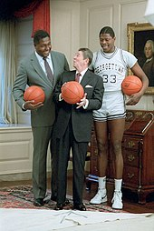 Two tall African-American men, one in a suit, one in a gray basketball uniform, stand behind a shorter elderly white male in an ornate room, with each man holding a basketball.