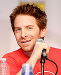 A man with red hair, smiling slightly and sitting behind a microphone