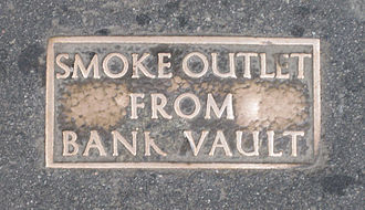 Frangibility - A plaque marking the frangible section of a London pavement, designed to be broken to release smoke in the case of an underground fire.