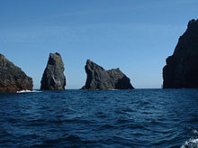 A series of dark black rocky shapes traverse from left to right in a dark blue sea under pale blue skies. The four main structures are tall and cliff-girt and set at odd angles to one another – the shapes are suggestive of a gathering of living creatures taken from a bestiary.
