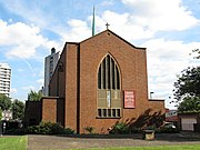 Tall rectangular brick church with arced stained glass window with external bell and copper spire.