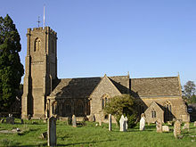 Stone building with square tower to the left hand end. In the foreground are gravestones.