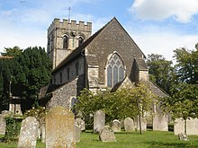 Rear view of a stone church with a castellated tower at the far end. The nearest side has very dark stone, two heavy buttresses and a three-light lancet window with trefoils. Trees surround the church on all sides, and there are several gravestones in front.