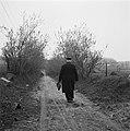 Suppoost met uniformpet en aktetas loopt over een pad, Bestanddeelnr 900-2418.jpg