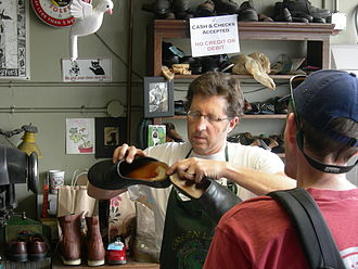 Craft - Shoes are repaired by a skilled shoemaker, here he evaluates a pair of shoes with a customer watching