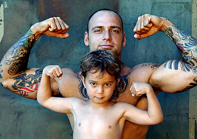 Some societies and academics place traditional gender roles (social norms for certain communities, while admiration or convention for others) as the most important component of machismo. Tattoo withchild.jpg