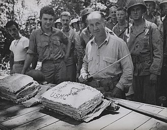 2nd Battalion, 1st Marines - Lt. Colonel William W. Stickney cuts a Thanksgiving cake with a Japanese officer's sword at Guadalcanal, as hungry Leathernecks look on.
