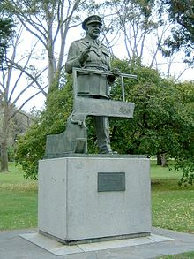 Bronze statue of a standing man in military uniform and peaked cap atop a stone base with a plaque at the front. He is clasping the window frame of a jeep.