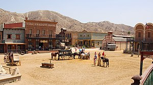 Squarish buildings made of wood and bricks surround a square, where horses and carriages gather.