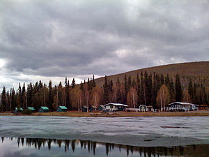 Scattered cabins are seen behind a lake with ice floating on its surface