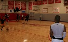 Picture of a gym with people playing basketball.