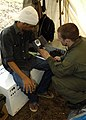 US Navy 050122-N-8539M-015 A Hospital Corpsman, assigned to USS Abraham Lincoln (CVN 72), checks the blood pressure of an Indonesian man at the Sultan Iskandar Muda Air Force Base, Banda Aceh, Sumatra, Indonesia.jpg