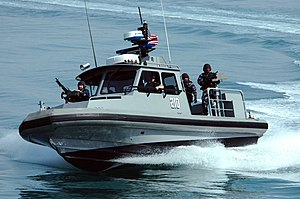 Structure of the United States Navy - Members of Inshore Boat Unit 24 patrol near Kuwait Naval Base.