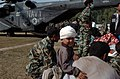 US Navy 051014-N-8796S-154 An injured Pakistani boy is carried by his father to a U.S. Navy MH-53E Sea Stallion helicopter where he will be transported to the city of Chaklala, Pakistan for medical treatment.jpg