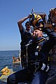 US Navy 060818-N-3390M-017 Chief Warrant Officer Mark Thomas and Hospital Corpsman 1st Class Rod Nudding, assigned to Mobile Salvage Unit One (MDSU-1), dress out in divers gear in preparation retrieving derelict fishing nets.jpg