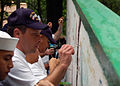 US Navy 070702-N-5525H-061 Postal Clerk 1st Class Larry Hobson, assigned to submarine tender USS Frank Cable (AS 40), paints a message of hope on the friendship wall outside of a regional children's rehabilitation center.jpg