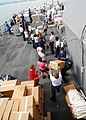 US Navy 080825-N-4044H-056 Sailors aboard the guided-missile destroyer USS McFaul (DDG 74) stack humanitarian assistance supplies to be put on pallets and then lifted from the ship to a crane barge and then given to the people.jpg