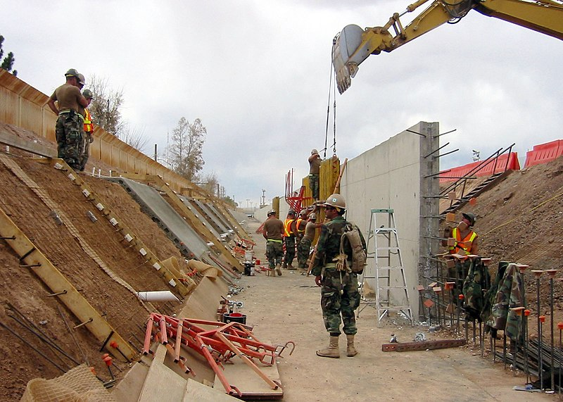 US Navy 090314-N-5253T-010 eabees assigned to Naval Mobile Construction Battalions (NMCB) 133 and NMCB-14 construct a 1,500 foot-long concrete-lined drainage ditch and a 10 foot-high wall to increase security along the U.S. and.jpg
