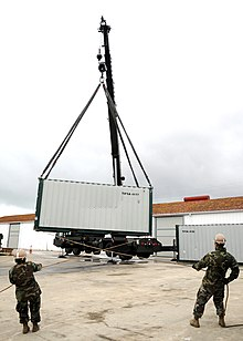 US Navy 100308-N-1120L-014 Seabees assigned to (NMCB) 7 use tag lines to steady a 20,000-pound load during a crane lift to load cargo onto a tractor trailer.jpg
