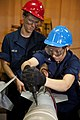 US Navy 110812-N-DX615-179 Aviation Ordnanceman 2nd Class Nadezda Coe tightens the tail assembly of a GBU-38 joint direct attack munitions 500-poun.jpg