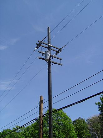 Utility pole - Standard utility pole in the United States. Electrical wires and transformer seen on top and cable/telephone wires lower down, demonstrating the worker safety zone for telephone/cable company workers.