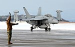 VAQ-132 Aviation Machinist's Mate signalling to crew of taxiing EA-18G Growler at Misawa 121228-N-VZ328-087.jpg