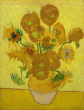 A ceramic vase with sunflowers on a yellow surface against a bright yellow background.