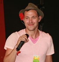 A man with a brown cap wearing a pink t-shirt and holding a microphone. He is looking to the left and smiling.