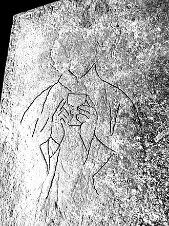 Mortehoe - Enhanced outline of figure incised on slab, showing chalice held to the chest and clerical vestments