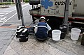 Worker Cleaning Old Starbucks Sign Letters on Sidewalk 20150613.jpg