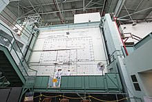 "Two workmen on a movable platform similar to that used by window washers, in front of a wall with arrays of holes and many wires running across it. A sign says ""Graphite Reactor loading face""."
