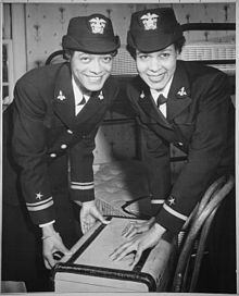 Two African-American WAVE officers in dress uniforms shutting a suitcase