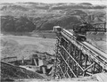 """""""The discharge end of the 200 foot conveyor boom in the gravel pit, straddling the conveyor running out on the... - NARA - 294029.tif"""