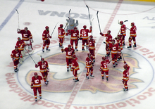 Twenty hockey players in red uniforms stand at centre ice with their sticks raised in salute to the crowd around them.
