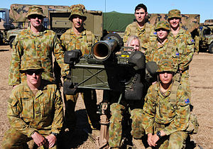Photograph of eight people wearing camouflage uniforms posing with a rocket launcher. Several camouflaged trucks are visible in the background.